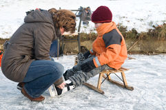 Going to skate. Mother helping her son putting on his iceskates Royalty Free Stock Photos