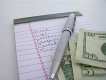 Going to the store. Macro of pen, money and shopping list stock photo