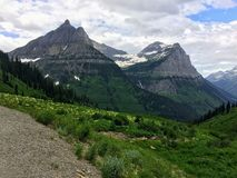 Going to the Sun Road, View of Landscape, snow fields In Glacier National Park around Logan Pass, Hidden Lake, Highline Trail, whi. Ch features waterfalls royalty free stock photo