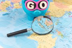 Going to Travel. Magnifier zoom spot on the map. Saving piggy bank with sunglasses and GO slogan staying on the world. Map royalty free stock photography