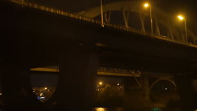 Going under the bridge at night, lights of passing cars stock video footage