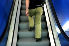 Going Up. Motion photo of man on escalator Stock Photo