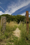 Going up. Small natural path between a wooden and iron post. Where will this path lead you Stock Photo