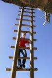 Going up. Young woman, climbing a big ladder upwards toward an overhang Stock Photography