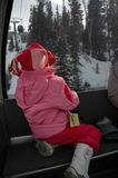 Going up. Child looks out window of Ski Lift. Winter vacation fun. Fun in the snow Stock Image