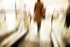 Going up. Female going up with the escalator in a department store - motion blur Royalty Free Stock Image