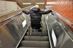 Going up the escalator with wheel chair stock images