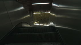 Going up on metro subway escalator towards the exit doors. stock video footage
