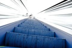 Going up on moving escalator to white light Royalty Free Stock Images