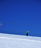 Going up on the slope. Image of a skier on a ski installation in Surianu sky resort, Romania Royalty Free Stock Photo