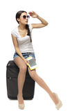 Going on vacations. Full length of young woman sitting on her travel bag and holding the tickets with passport looking faraway isolated on white background Stock Photos