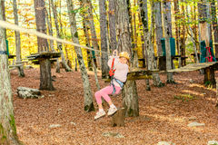 Going on zip line. Little girl is going on zip line in adventure park royalty free stock images
