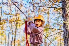 Going on zip line. Little girl is zip lining in adventure park stock photos