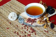 Goji莓果,中国日期,距骨根编结与一碗在红色背景的药草浸剂 侧视图 库存图片