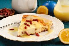 自创乳酪蛋糕用柠檬酱、柠檬和goji莓果 免版税库存照片