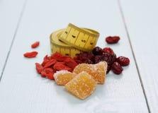 Goji bär, tranbär, kanderad ingefära och måttband Royaltyfri Fotografi