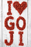 Goji berries as a heart and letters on old white wooden table. Stock Images