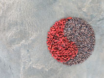 Goji berries and cacao nibs in Yin Yang shape. Organic goji berries and cacao nibs shaped in a Yin Yang symbol and placed on a vintage wooden table Royalty Free Stock Photos