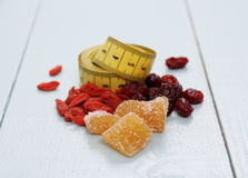Goji berries, cranberry, candied ginger and tape measure Royalty Free Stock Photography