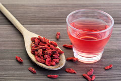 Goji berries. Dried goji berries in a wooden spoon with a small cup of tea on the side stock photos