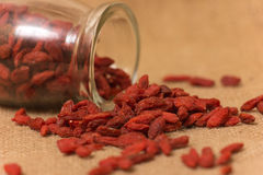 Goji berries. In glass bottle on a burlap sack stock images