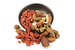 Goji Berries and Nuts Spilling from a Bowl Stock Photography