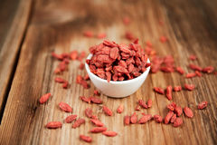 Goji berries in a white china bowl on a table. Goji berries super food with antioxidants, minerals and vitamins in a white china bowl on a brown wooden table royalty free stock photo