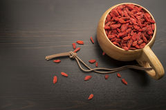 Goji berries in a wooden bowl, around which are scattered on the black berry table Stock Photo