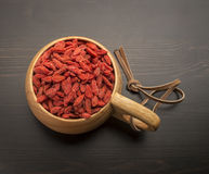 Goji berries in a wooden bowl, which stands on a black table Royalty Free Stock Image