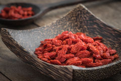 Goji berries on wooden plate and spoon Royalty Free Stock Image