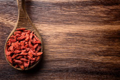 Goji berry. Goji berries on a wooden spoons, wooden brown background Stock Photography