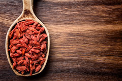 Goji berry. Goji berries on a wooden spoons, wooden brown background Royalty Free Stock Photo