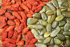 Goji berry dry fruits and pumpkin seeds, on a wooden table Royalty Free Stock Photography