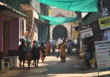 GOKARNA卡纳塔克邦印度- 2016年1月29日:黄色传统印地安莎丽服的印地安妇女步行沿着向下拥挤街道的在Gokar 图库摄影