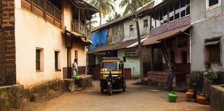 Gokarna,卡纳塔克邦,印度2014年1月29日-黄色人力车和当地人有水罐的水在街道 库存图片