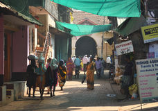 GOKARNA IL KARNATAKA INDIA - 29 GENNAIO 2016: Donna indiana in sari indiani tradizionali gialli che cammina giù la via ammucchiat Fotografia Stock