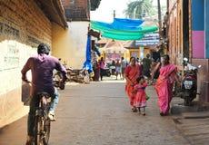 GOKARNA KARNATAKA INDIA - 29 JANUARI 2016: Indische vrouwen met een meisje die heldere saris dragen die neer in de straat in Goka Royalty-vrije Stock Afbeelding