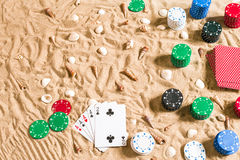 Gokkend op vakantieconcept - wit zand met zeeschelpen, gekleurde pookspaanders en kaarten Hoogste mening royalty-vrije stock afbeeldingen