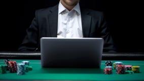 Gokker het letten op het wedden op laptop de toepassing van het computercasino, pook, verslaving royalty-vrije stock foto's