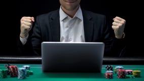 Gokker het spelen op laptop en het tonen van succesgebaar, winnend weddenschap, fortuin stock foto