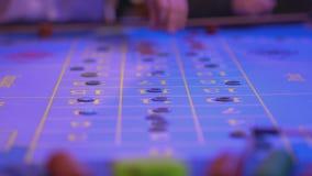 Gokkers gezette gokkenspaanders op roulettelijst stock footage
