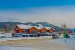 GOL NORWAR, APRIL, 02, 2018: Övervintra den utomhus- sikten av röda träbyggnader som lokaliseras i dowtown som täckas med snö und Arkivfoton