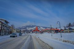 GOL, NORWAR, APRIL, 02, 2018: Outdoor view of wooden building and some cars located at one side of the road close to a. Gas station, covered with snow in GOL stock photography