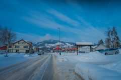 GOL, NORWAR, APRIL, 02, 2018: Outdoor view of wooden building and some cars located at one side of the road close to a. Gas station, covered with snow in GOL Royalty Free Stock Photography