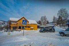 GOL NORWAR, APRIL, 02, 2018: Utomhus- sikt av gul träbyggnad som täckas med snö, och några bilar som parkeras i Fotografering för Bildbyråer