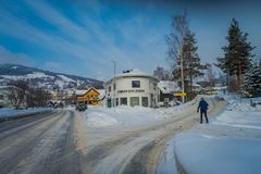 GOL, NORWAR, APRIL, 02, 2018: View of woman walking to the building of veterinary located in dowtown between two streets. In a Y intersection covered with snow Stock Photo