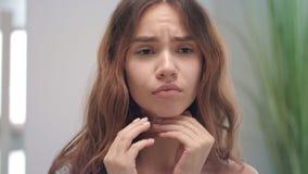 Gola irritata di sensibilità turbata della donna e toccare lo specchio anteriore del bagno del collo della pelle video d archivio