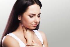 Gola irritata Giovane donna con la gola irritata Freddo ed influenza Tiene la sua mano alla gola Sensazioni dolorose Il concetto  Immagine Stock Libera da Diritti