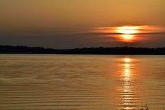 Gold与在右边部分地掩藏的太阳的湖日落 库存图片