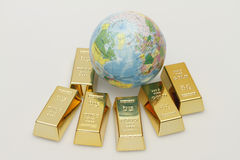 Gold. A small globe lies between six gold bars Stock Images